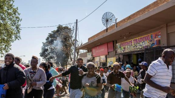 South African looters run off an alleged foreign-owned shop as South African Police officers intervene during a riot in the Johannesburg suburb of Turffontein on September 2, 2019 as angry protesters loot alleged foreign-owned shops in a new wave of violence targeting foreign nationals. (Photo by GUILLEM SARTORIO / AFP)        (Photo credit should read GUILLEM SARTORIO/AFP/Getty Images)