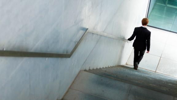 BERLIN, GERMANY - AUGUST 07: A man wearing a business suit walks down the stairs on August 07, 2014 in Berlin, Germany. (Photo by Thomas Trutschel/Photothek via Getty Images)