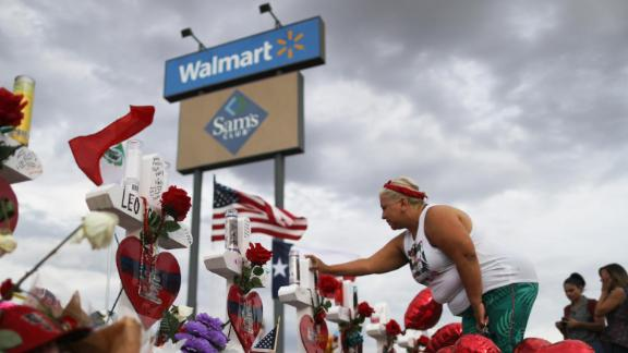 EL PASO, TEXAS - AUGUST 06:  A woman touches a cross at a makeshift memorial for victims outside Walmart, near the scene of a mass shooting which left at least 22 people dead, on August 6, 2019 in El Paso, Texas. A 21-year-old white male suspect remains in custody in El Paso, which sits along the U.S.-Mexico border. President Donald Trump plans to visit the city August 7. (Photo by Mario Tama/Getty Images)