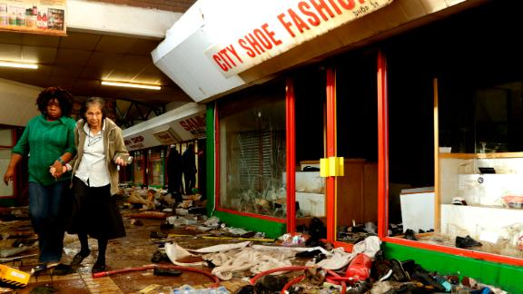A shoe shop owner is helped by a staff member to inspect the damage caused by looters in Germiston, east of Johannesburg, South Africa.