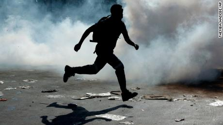 A man runs from tear gas  in Germiston, east of Johannesburg, South Africa.
