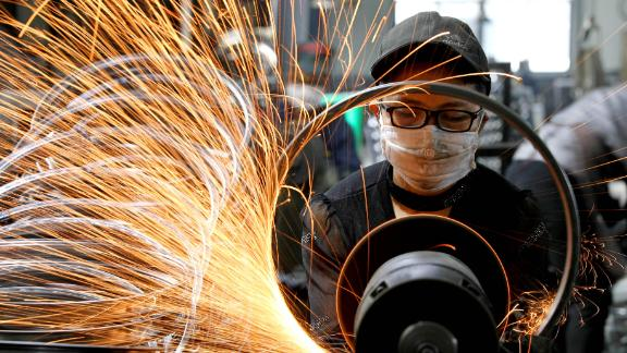 A worker welds bicycle steel rims at a workshop in Tianmushan town on September 2, 2019 in Hangzhou, Zhejiang Province of China.
