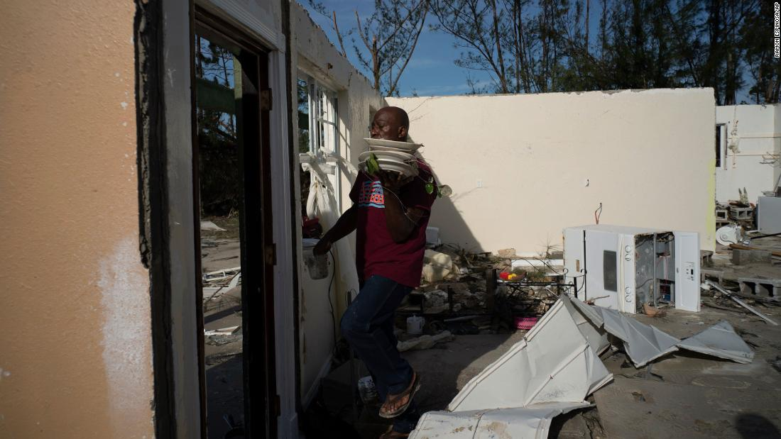 A resident recovers dishes from his son's home in Pine Bay, Bahamas, on September 4.