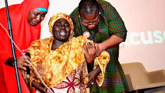 Rebeca Samuel (C), the mother of Sarah Samuel, one of the abducted Chibok girls, breaks down in tears while being helped by Coordinator of Bring Back Our Girls, Oby Ezekwesil (R), and Aisha Yesufu during a lecture in Abuja marking the third anniversary of the abduction in 2017.