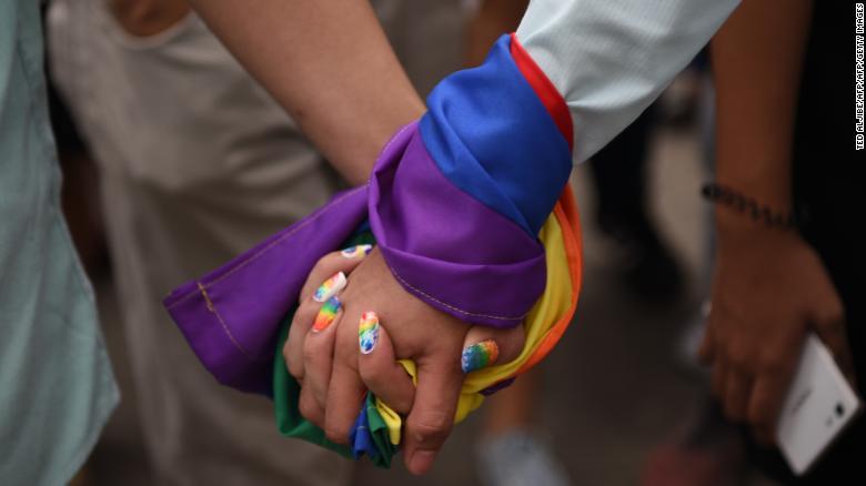 Um casal de mãos dadas envolto em uma bandeira do arco-íris durante uma marcha de orgulho na cidade de Marikina, leste de Manila, em 30 de junho de 2018.