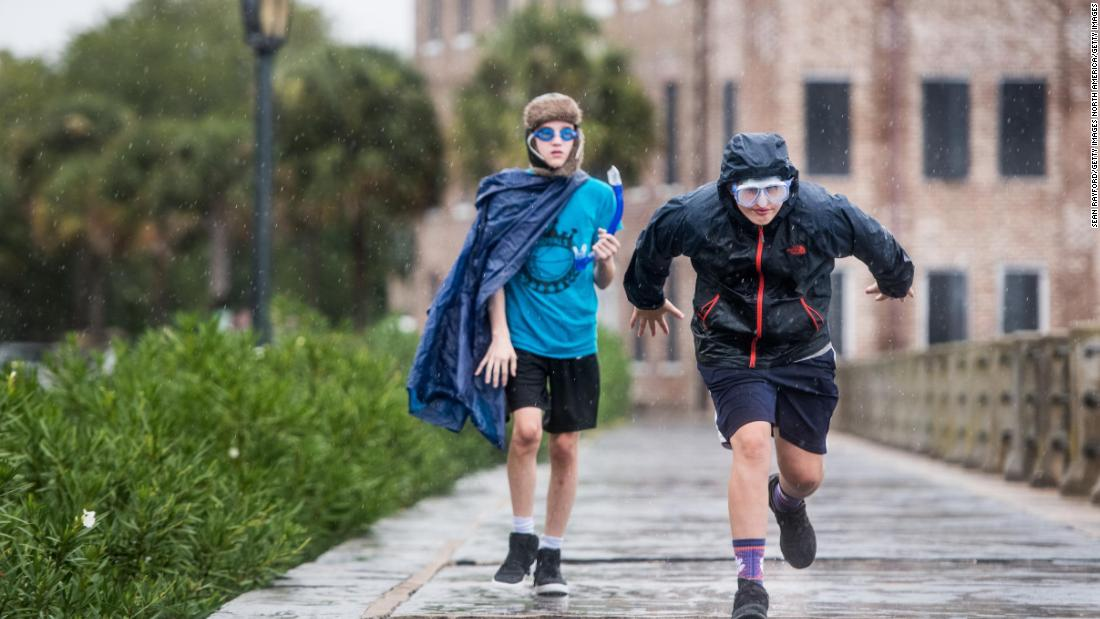 Braden Vick, right, runs along the Charleston Battery as Scott Ray follows behind on September 4 in Charleston, South Carolina.  Hurricane Dorian hit the area Thursday, September 5.