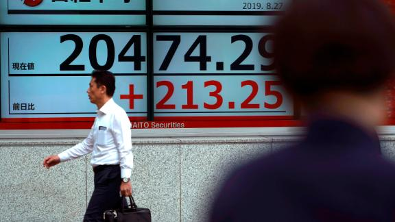 A man walks past an electronic stock board showing Japan's Nikkei 225 index at a securities firm in Tokyo Tuesday, Aug. 27, 2019. Asian shares mostly rose Tuesday as investors found reason to be cautiously optimistic again about the potential for progress in the costly trade war between the U.S. and China. (AP Photo/Eugene Hoshiko)