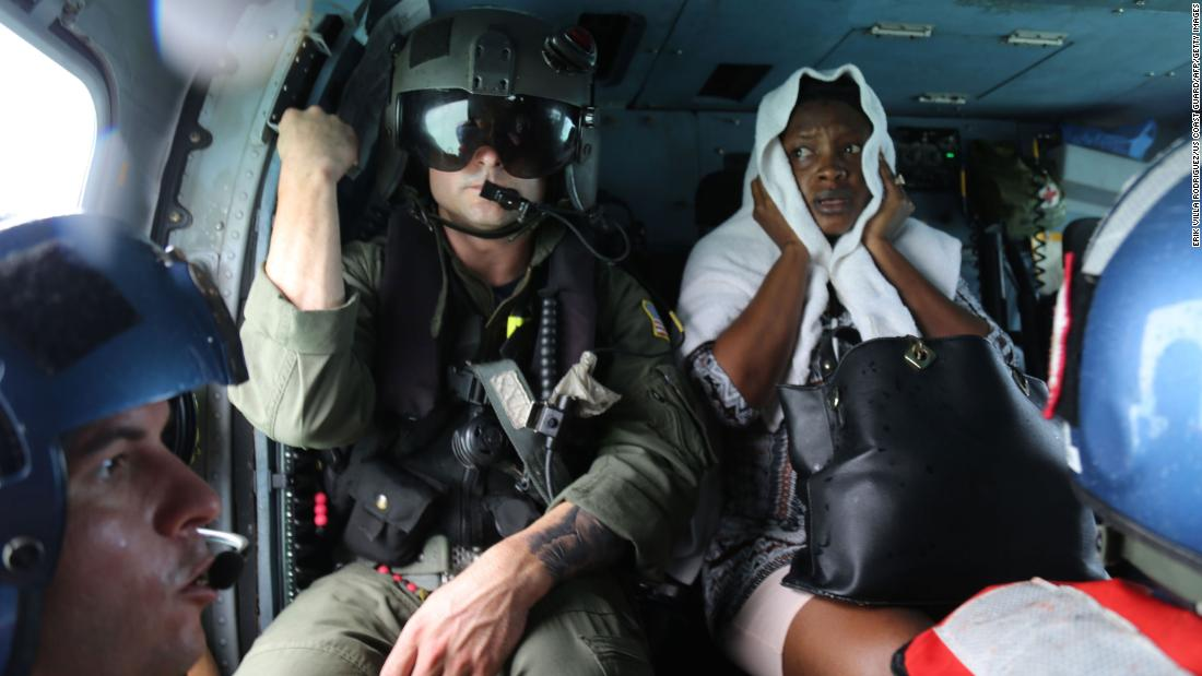 A woman is evacuated in a Coast Guard helicopter after being rescued from Treasure Cay, Bahamas, on Wednesday, September 4.