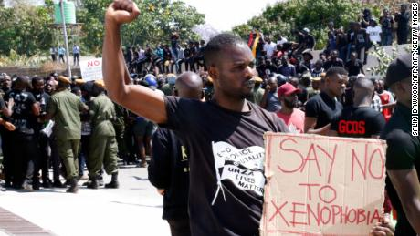 A protestor gestures and holds a placard during a demonstration in front of the South African Embassy in Lusaka, Zambia on September 4, 2019