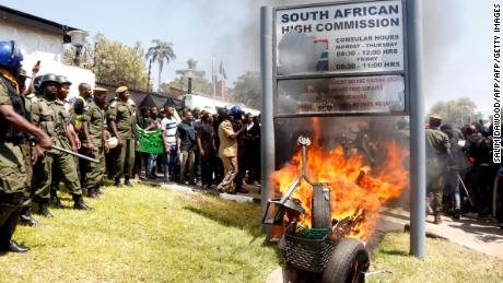 Zambia's university students burn the sign outside the South African Embassy in Lusaka on September 4, 2019 during a demonstration to protest against xenophobic attacks on foreign nationals in the Rainbow Nation. (Photo by SALIM DAWOOD / AFP)