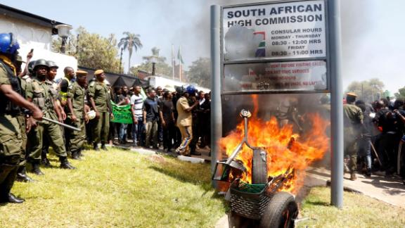 Zambia's university students burn the sign outside the South African Embassy in Lusaka on September 4, 2019 during protests against xenophobic attacks on foreign nationals in the Rainbow Nation.