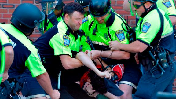 """Boston Police officers arrest an anti-parade demonstrator during the """"Straight Pride"""" parade in Boston, on August 31, 2019. - """"Straight Pride"""" advocates who support President Donald Trump and counter-demonstrators who consider them homophobic extremists staged dueling rallies in Boston on Saturday. (Photo by Joseph PREZIOSO / AFP)        (Photo credit should read JOSEPH PREZIOSO/AFP/Getty Images)"""