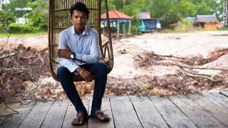 Sina, the son-in-law of Sok Sabay Resort's owner, sits on a veranda that used to look out onto a pretty pond. It has now been filled out to make way for a construction site.