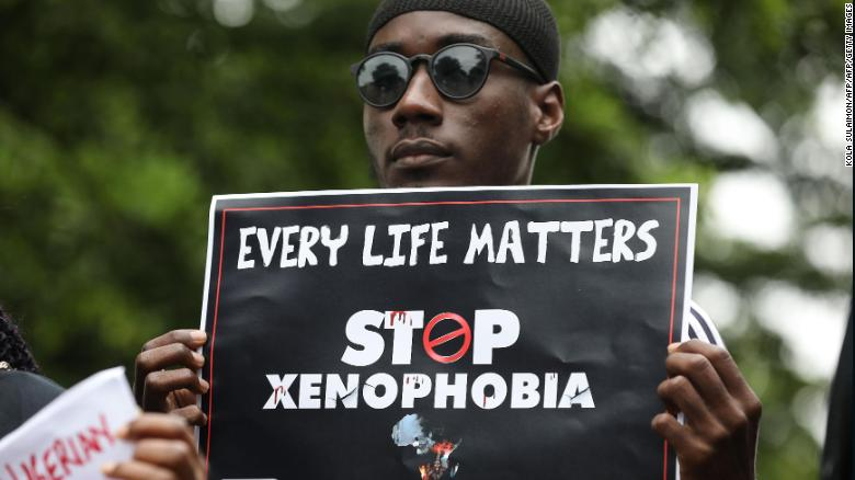 A demonstrator holds a sign during a protest against xenophobia outside of the main gate of the South African High Commission in Abuja, Nigeria.