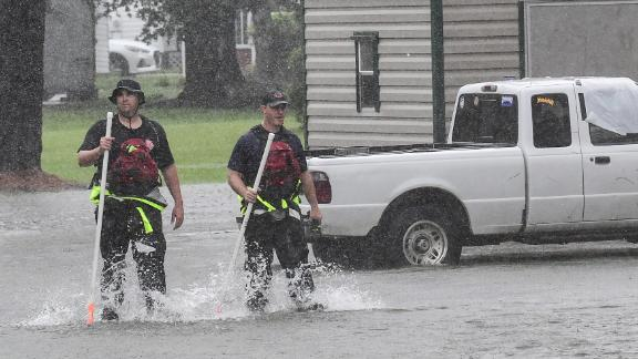Rescue workers walk through floodwaters in Little River, South Carolina, on September 5.