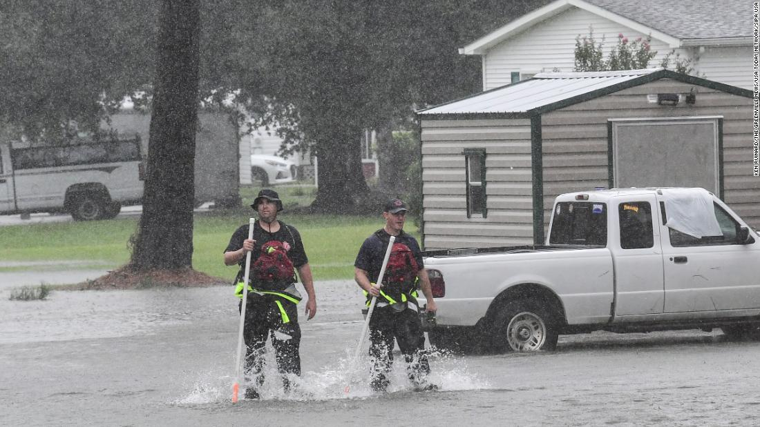 Horry County Fire Rescue walk through water checking a neighborhood starting to flood in Little River, near North Myrtle Beach, South Carolina, on September 5.