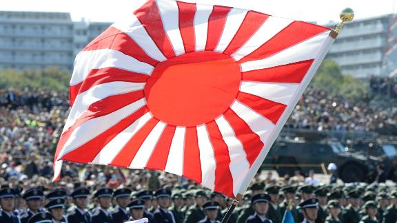 A soldier holds a Rising Sun flag during the military review at the Ground Self-Defence Force's Asaka training ground on October 27, 2013.
