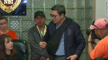 Chief of the NBI's International Airport Investigation Division Manuel Dimaano demonstrates the bag used to conceal the baby.