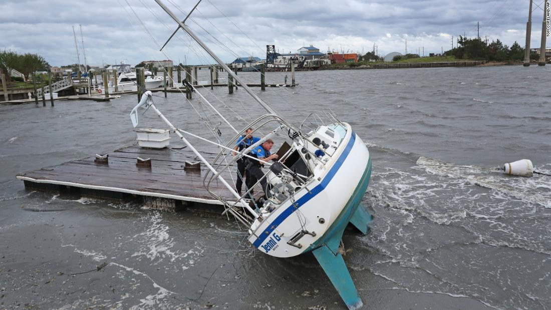 Beaufort Police Officer Curtis Resor, left, and Sgt. Michael Stephens check a sailboat for occupants in Beaufort, North Carolina, on September 6.