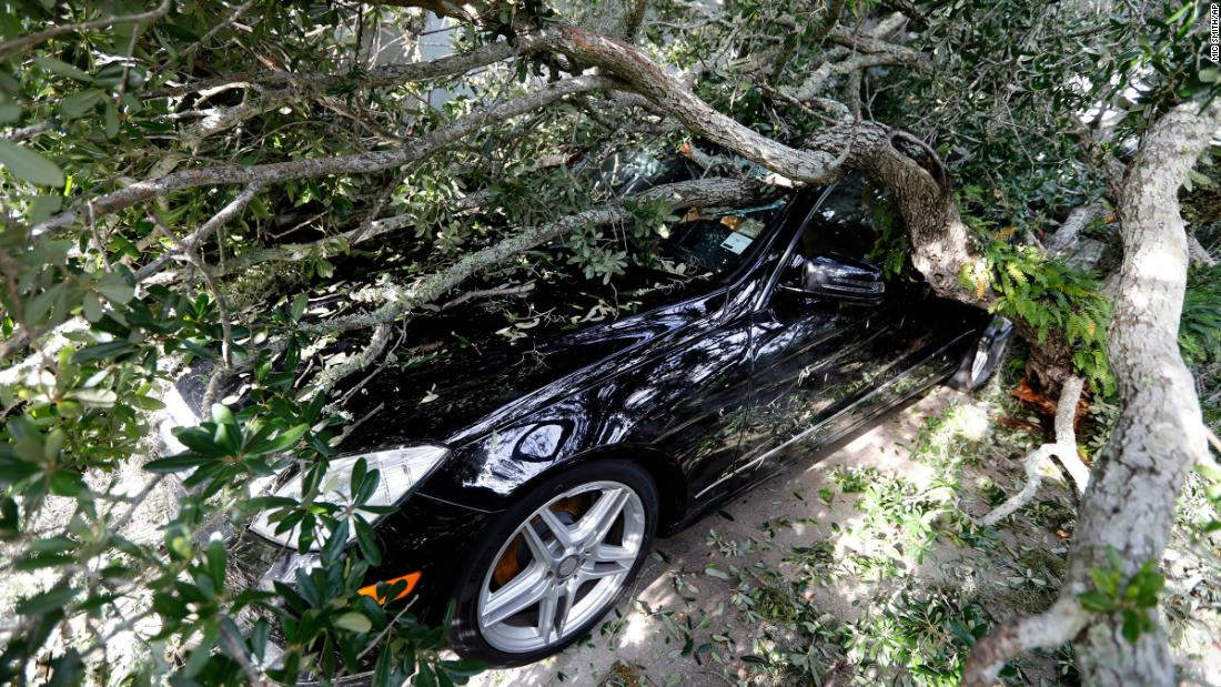 A fallen tree lies on top of a vehicle in Isle of Palms, South Carolina, on September 6.