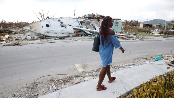 Schemelda Saintilien walks past debris and damaged houses on the Bahamas