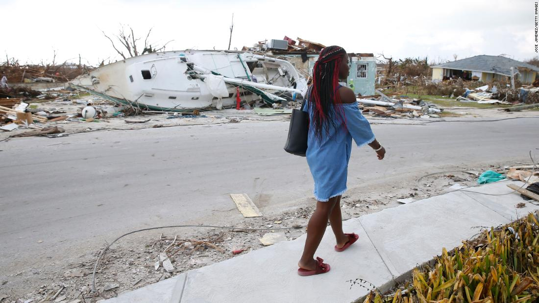 Schemelda Saintilien walks past debris and damaged houses on Great Abaco Island on September 6.
