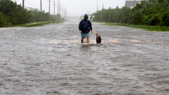 Bryan Philips walks with his dog on a flooded road in Salvo, North Carolina, on September 6.
