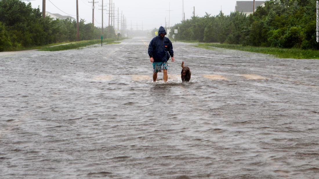 Bryan Philips walks with his dog on a flooded road in Salvo, North Carolina, as Hurricane Dorian hit the Outer Banks on Friday, September 6.