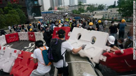 Protesters move barricades to block a street during the June 12 protest.