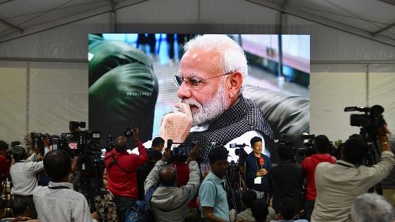 Members of the media cover the development as India's Prime Minister Narendra Modi is seen on a tv screen as he watches the live broadcast of the soft landing of spacecraft Vikram Lander of Chandrayaan-2 on the surface of the Moon at ISRO Telemetry, Tracking and Command Network (ISTRAC) centre in Bangalore early on September 7, 2019. - India lost communication with its unmanned spacecraft on September 7 just before it was due to land on the Moon, in a major setback to the country's lunar ambitions amid renewed interest in Earth's satellite. (Photo by Manjunath Kiran / AFP)        (Photo credit should read MANJUNATH KIRAN/AFP/Getty Images)
