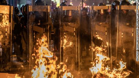 The riot police stand in front of a barricade set on fire by protesters following the dispersal of crowds outside the Mong Kok police station on September 7.