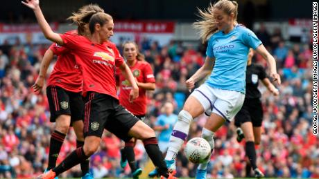 Abbie McManus tackles Janine Beckie during the Manchester derby.