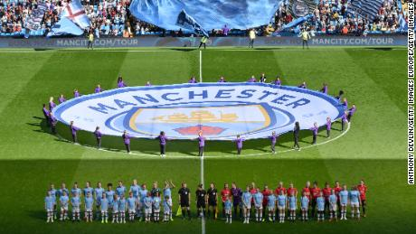 The two teams line up prior to the historic first meeting between the Manchester clubs.