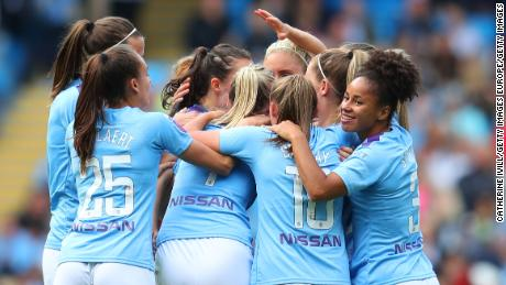 Manchester City players mob Caroline Weir after her goal.