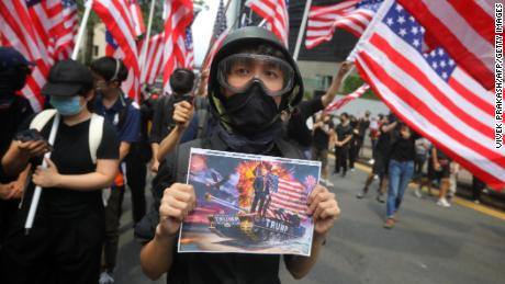 A man holds a placard as protesters wave US national flags while they march from Chater Garden to the US consulate in Hong Kong on September 8.
