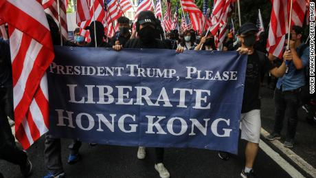 Protesters hold a banner and wave US national flags as they march from Chater Garden to the US consulate in Hong Kong on September 8, 2019, to call on the US to pressure Beijing to meet their demands and for Congress to pass a recently proposed bill that expresses support for the protest movement. - Pro-democracy activists planned to rally outside the US consulate in Hong Kong on September 8 as the they try to keep international pressure on Beijing following three months of huge, sometimes violent, protests. (Photo by Vivek Prakash / AFP)        (Photo credit should read VIVEK PRAKASH/AFP/Getty Images)