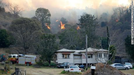 Fire and emergency crew battle a bushfire near a house in the rural town of Canungra in southeast Queensland, Australia, on September 6, 2019.