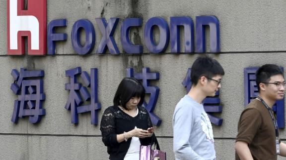 People walking past a Foxconn logo in Taipei.