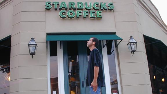 Winter stands in front of one of the more than 15,000 Starbucks he has visited.