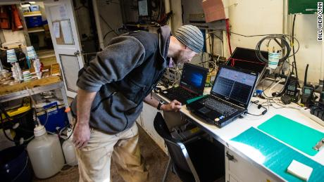 Ryan McCabe, on board a NOAA research vessel, examines data from the warming Arctic seas.