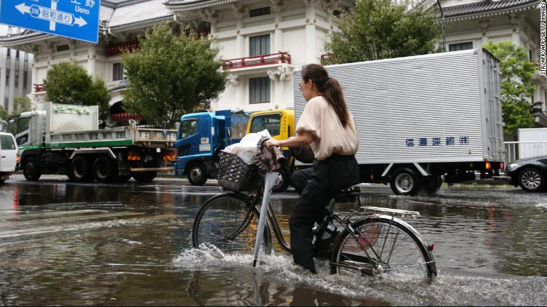 A woman cycles through a flooded area in Tokyo on September 9, 2019.