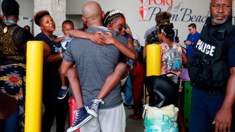 Mark Winder of Tampa, Florida, embraces his niece, Gabriella Winder, 10, as she and her family arrive in Riviera Beach, Florida, from the Bahamas on Saturday, September 7.