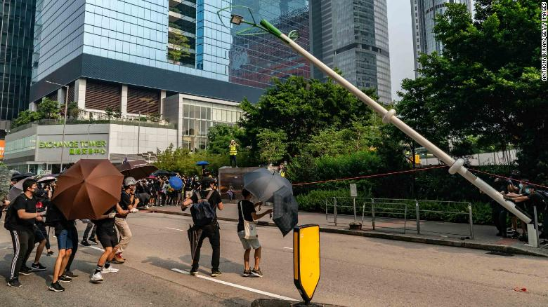 """Protesters attempt to pull down a """"smart"""" lamp post during an anti-government rally in Hong Kong on August 24."""
