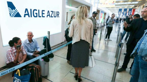 Passengers wait in front of the French airline Aigle Azur reception desk, without any employees, at Orly airport in Paris last week  (Photo by Michel Stoupak/NurPhoto via Getty Images)