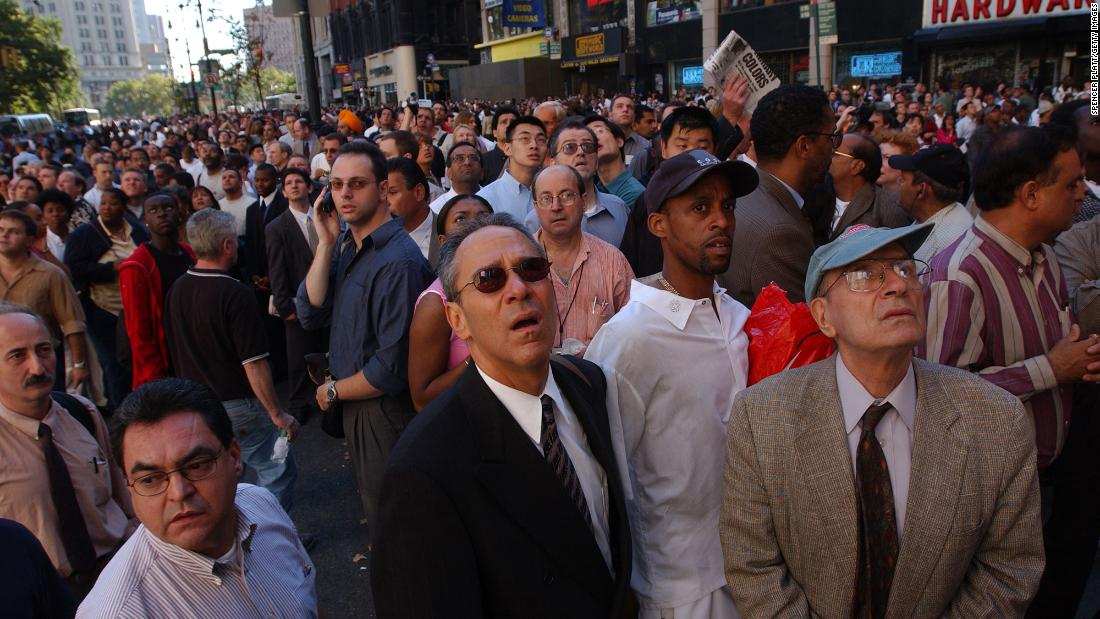 People in New York look up as the World Trade Center burns.