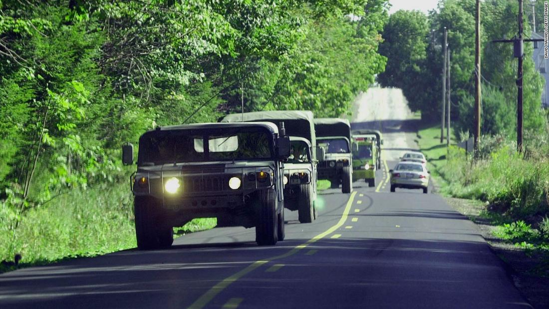 Military vehicles travel along the road leading to the crash site of Flight 93.