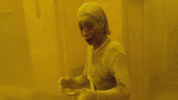 "Marcy Borders stands covered in dust as she takes refuge in an office building after one of the World Trade Center towers collapsed. Borders, who became known as ""Dust Lady,"" died of stomach cancer in 2015. She was 42."