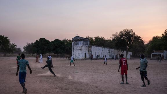 Teenagers play football in front of the church of Birao, northern Central African Republic.