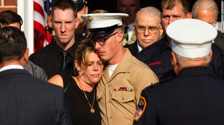 Michael Haub comforts his mother, Erika Starke, as they attend a funeral service for his father,  firefighter Michael Haub.