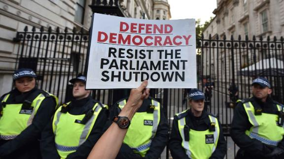 A protester holds a placard at the gates of Downing Street during a demonstration against the UK Government's decision to  prorogue parliament.